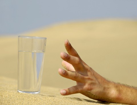 Hand is reaching for a fresh glass of cold water in desert.