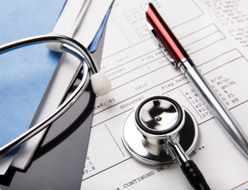 stethoscope and pen resting on a sheet of medical lab test results, with patient file and x-ray or mri film